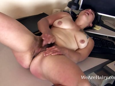 Shaggy Valerie plays with her hirsute snatch at her desk